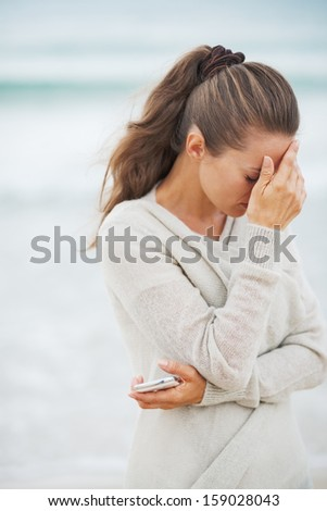 Stressed young woman in sweater on beach with mobile phone