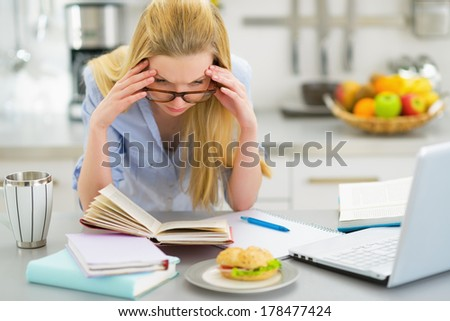Stressed young woman studying in kitchen - stock photo