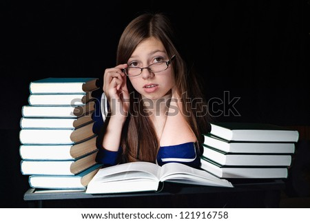Stressed young woman wearing eyeglasses sitting at a table among books on a black background - stock photo