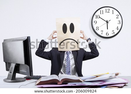 Stressful anonymous businessman scratching his head in office - stock photo