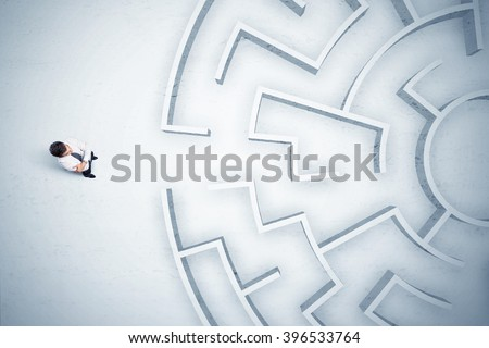 Stressful business man looking at circular maze with nowhere to go