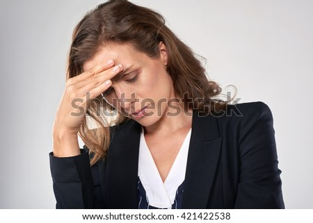 Stressful business woman is suffering from painful headache, sad depressed and upset - stock photo