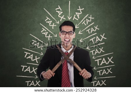 Stressful businessman having tax problems and try to cut his neck - stock photo