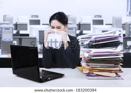 Stressful businesswoman in office with laptop and stacks of files
