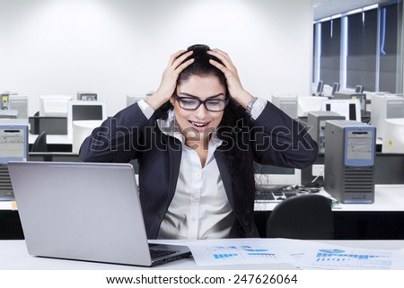 Stressful businesswoman shouting at her job on the table, shot in the office - stock photo
