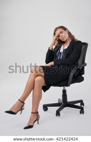Stressful businesswoman sitting in office chair, having a bad headache migraine - stock photo