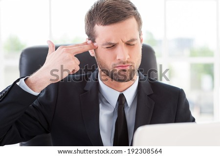 Stressful day. Depressed young man in formal wear touching his temple with finger gun and keeping eyes closed while sitting at his working place - stock photo
