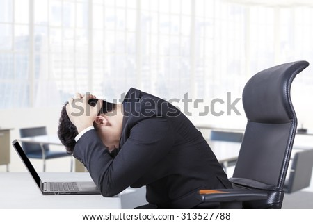 Stressful entrepreneur sitting in the office chair with a laptop on the table and holding his head - stock photo