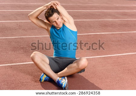 Stretch higher. Handsome young sportsman sitting and holding his arms behind while stretching - stock photo