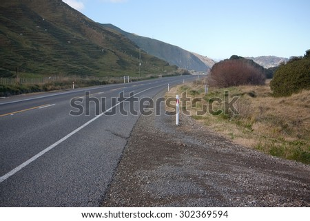 stretch of coastal road shaded by dune like pastoral farming hills, winter, Gisborne, East Coast, North Island, New Zealand  - stock photo