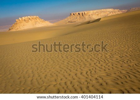 Stretch of dune ripples with a lime stone hill in the background - stock photo