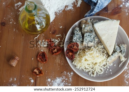 Stretched and uncooked homemade pizza dough with tomato sauce, bacon  and three types cheese with dried tomatoes on a kitchen towel, ready for ingredients. Taken on a rustic wooden table with flour. - stock photo
