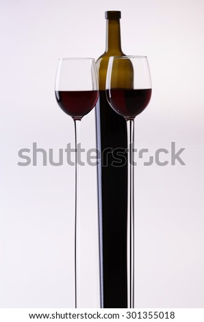 Stretched bottle and two glass goblets with red grape wine standing close to each other in studio isolated on white backgroung, vertical picture - stock photo