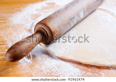 stretched dough with a rolling pin and flour - stock photo
