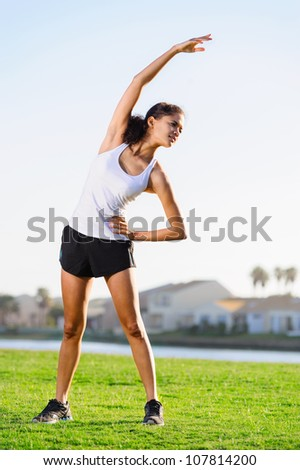 Stretching athlete warming up for a workout outdoors. healthy fitness lifestyle - stock photo