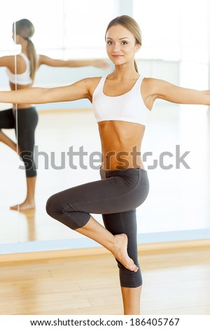 Stretching before her workout. Young beautiful woman in sportswear stretching