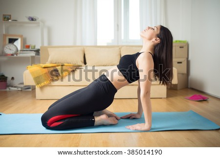 Stretching fitness and pilates exercise on yoga mat.Toning waist and abs,getting in shape for summer.Practicing yoga and pilates in small improvised home space.Exercise that you can do at home. - stock photo