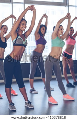 Stretching girls. Young beautiful cheerful women with perfect bodies in sportswear doing stretching with smile while standing in front of window at gym - stock photo