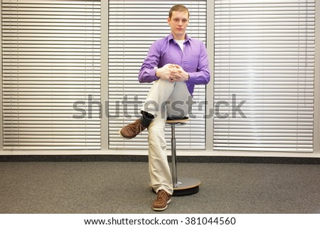 stretching legs in office -  man sitting on pneumatic stool exercising - stock photo