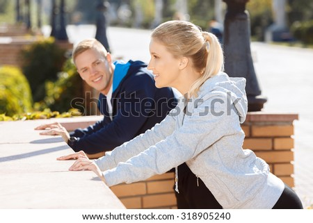 Stretching of young couple before morning training outdoors - stock photo