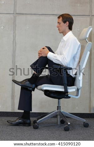 stretching on chair in office - business man exercising  - stock photo