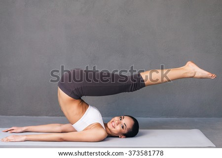 Stretchy beauty. Side view of beautiful young African woman in sportswear practicing yoga and looking at camera with smile while lying on exercise mat against grey background - stock photo