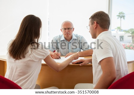 Strict boss sitting at the table and looking on his subjects