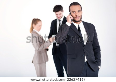 Strict business call. Successful and smiling African businessman talking on cell phone while his colleagues are working on a tablet in the background on a gray background