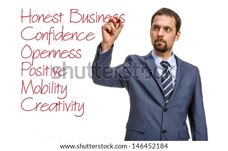 strict entrepreneur describes the basic principles of doing business / attractive man in an expensive suit writing the words of a red marker - isolated on white background