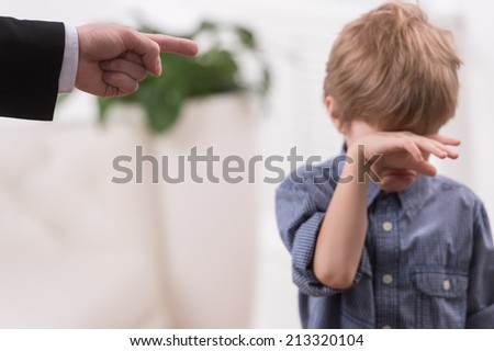 Strict father discipline naughty son. Isolated on white background boy wiping tears - stock photo