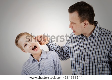 Strict father punishes his son. - stock photo