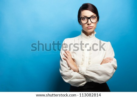 Strict woman in large glasses, blue background - stock photo