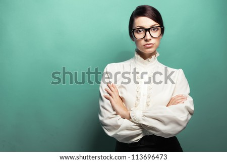 Strict woman in large glasses, green background