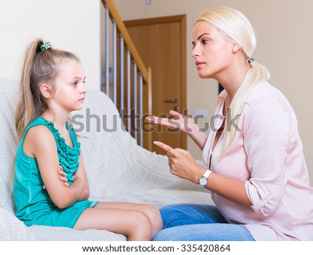 Strict young mother scolding mischievous little girl at home