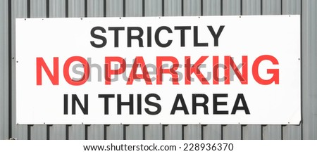 Strictly No Parking sign written on a metal wall. - stock photo