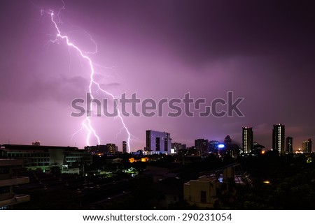 Strike of lightning into building in city. - stock photo