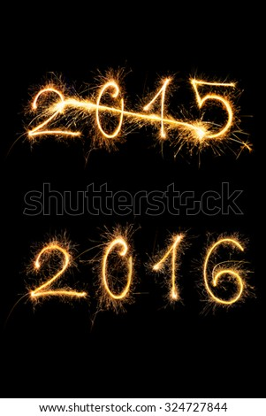 Strikethrough 2015 and 2015 digits made of sparkling light isolated on black background. Old year going, new year comming.