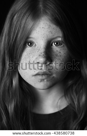 Striking black and white portrait of young girl with freckles