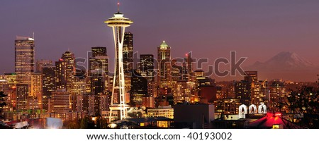 Striking panoramic image of Seattle skyline with Mount Rainier glowing at sunset - stock photo