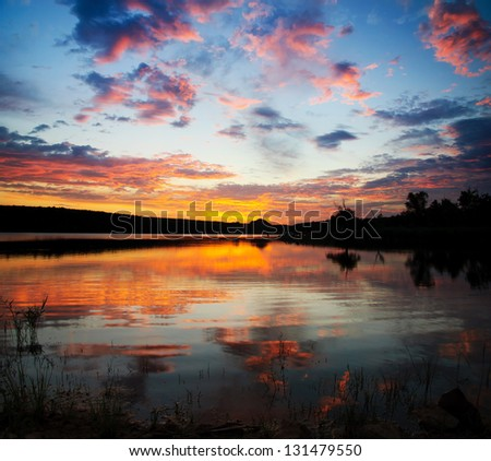 Striking sunset above the lake with bright clouds and sky - stock photo