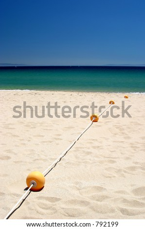 String of buoys or beach markers on sunny hot tarifa beach in Southern Spain Tarifa beach is popular for kitesurfing and windsurfing holidays and vacations