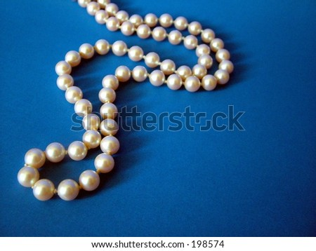 String of pearls on dark blue background - stock photo