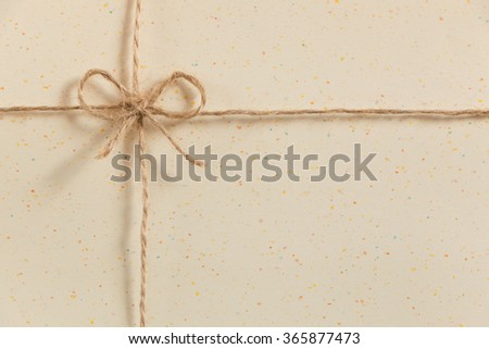 string or twine tied in a bow on point  paper brown background