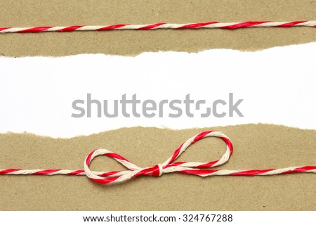 String red and white on brown wrapping paper with copy space background - stock photo
