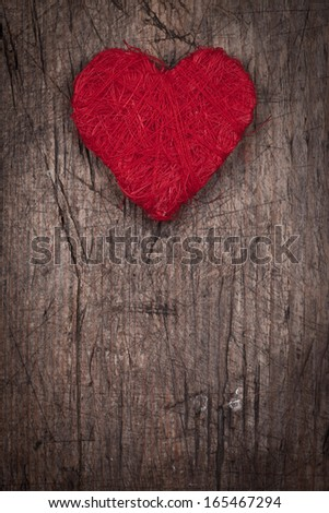 String red heart on wooden background, concept