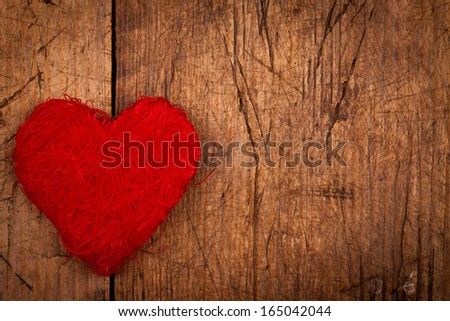 String red heart on wooden background, left side