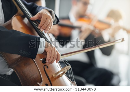 String section of classical music symphony orchestra performing, cellist playing on foreground, hands close up - stock photo