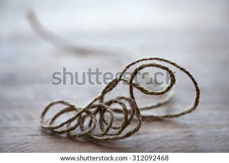 String theory represented with a hemp string. String theory concept image.  Multiple spiral of extra dimensions curled up in space. Extremely shallow depth of field. - stock photo
