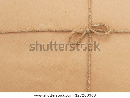 String tied in a bow over brown paper packaging.