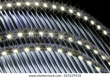 Strip LEDs shine over the corrugated metal. - stock photo